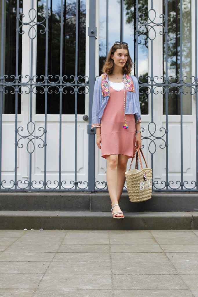Die neue Reihe Just Be Yourself startet im Juli mit dem Motto: Summer Sale. Katharina von Some Kind of Fashion zeigt dazu ein Outfit mit bestickter Jacke mit PomPoms und einem Kleid mit Muschelkante am Ausschnitt. Passend zur Location ist das Outfit in bunten Pasteltönen gehalten.