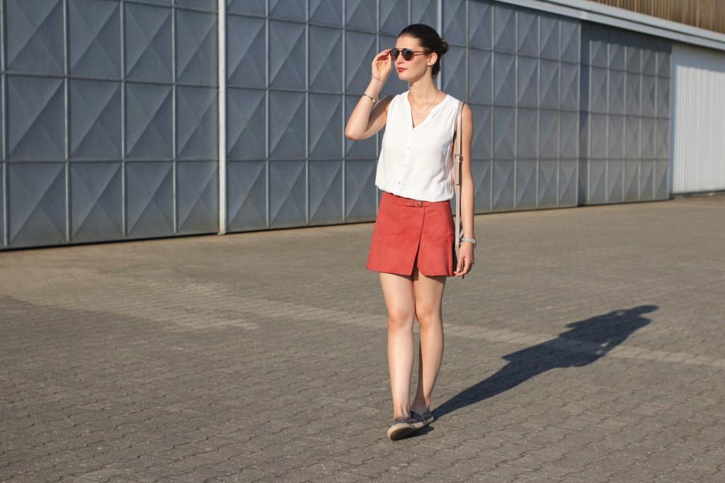 Katharina von Some Kind of Fashion trägt im Spätsommer einen asymetrischen Wildlederrock in Orange. Dazu kombiniert sie ein weiches Blusenshirt in Weiß und Espadrilles in Schlangenlederoptik.