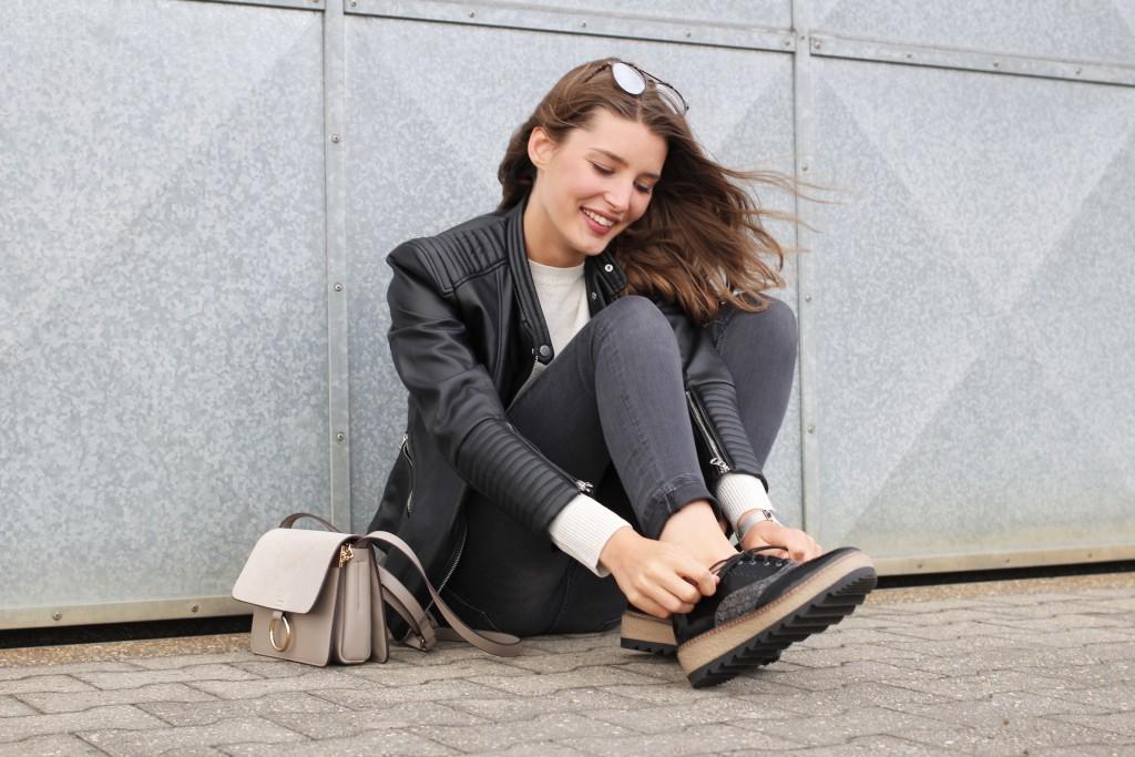 Im Herbst setzt Katharina von Some Kind of Fashion auf Plateau-Sneakers als modisches Must-Have. Dazu kombiniert sie graue Jeans, Lederjacke und Strick in hellbeige. Damit ist man im Herbst stylisch und bequem unterwegs.