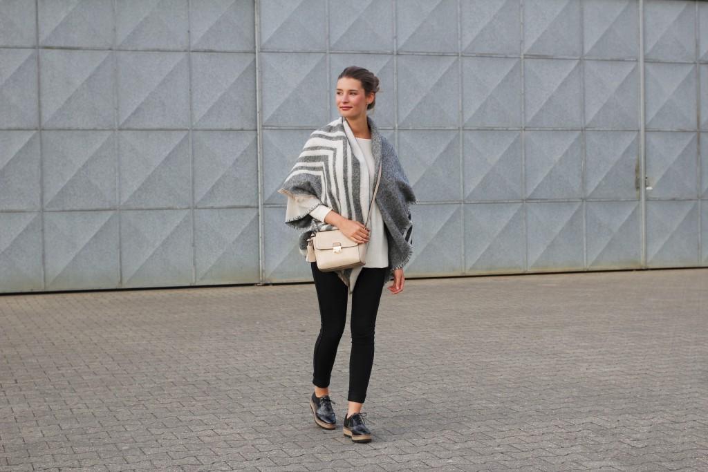 Herbstzeit ist Ponchozeit. Katharina von Some Kind of Fashion hat sich für ein Modell in Grau und Beige entschieden, das sie zu kuschligen Strickpullover, schwarzer Jeans und Plateau-Sneakers kombiniert.