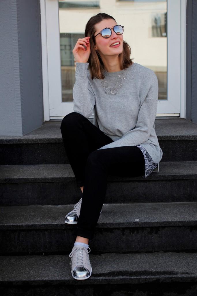 Mit verschiedenen Lagen in einem Look bekommt man gleich einen ganz anderen Eindruck von einem Outfit. Bloggerin Katharina peppt so ein schlichtes graues Outfit mit einer Lage in Schlangprint auf. Dazu wählt sie silberne Details und Adidas Superstars Metal Toe.