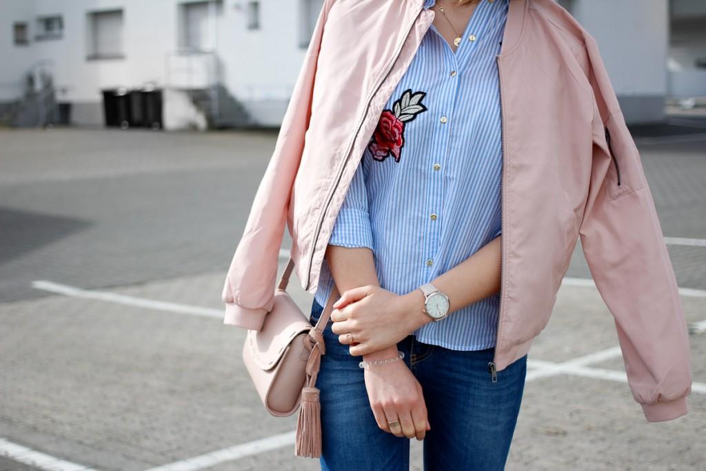 Bomberjacken waren schon im letzten Jahr groß in Mode. Die coolen Modelle bleiben uns aber auch in 2017 erhalten und lassen sich in Pastellfarben wunderbar für den Frühling einsetzen. Bloggerin Katharina kombiniert ihr rosa Bomberjacke mit eine hellblauen Bluse mit Blumen-Patches und Bluejeans - richtig frühlingshaft!