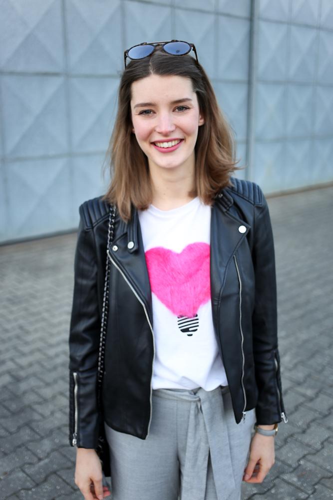 Raus aus der Komfortzone war das Motto bei diesem Look von Bloggerin Katharina. Sie kombiniert graue Culottes zu weitem oversize Shirt mit einem pinken Plüsch-Herz als Eyecatcher.