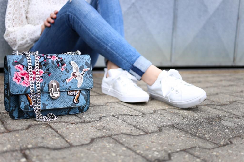 Spitzenbluse und Lack-Sneaker mit Satinschleife weiß