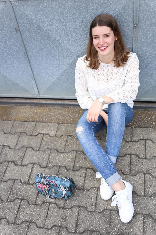 weiße Spitzenbluse und Lack-Sneaker mit Satinschleife
