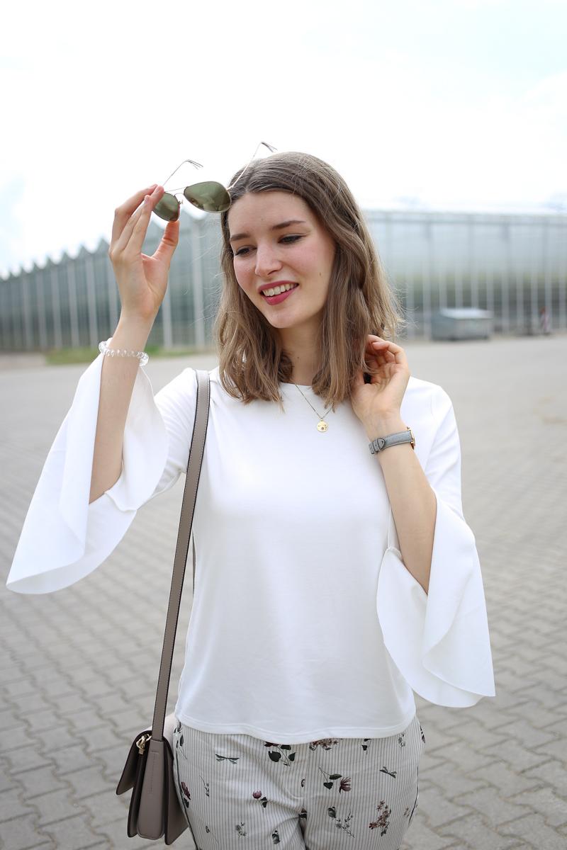 Angefixt durch eine Freundin hat sich Bloggerin Katharina von Some Kind of Fashion vor Kurzem diese süße Blumenhose gekauft. Im Sommer passt sie perfekt zu hellen Oberteilen und Sandalen. Bei den Farben ist Katharina bei hellem Beige, Weiß und Khaki geblieben und sie setzte Akzente durch Details an den Ärmeln.