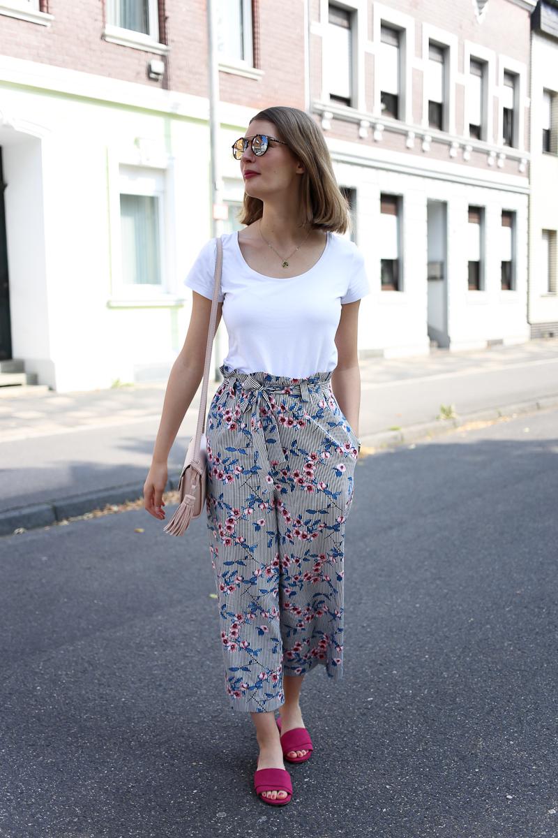 Bloggerin Katharina wählt für ihr Spätsommer-Outfit eine geblümte Culottes mit weißem Basic-Shirt und auffälligen pinken Pantoletten. Ein entspannter City-Look mit Muster und Farbe.