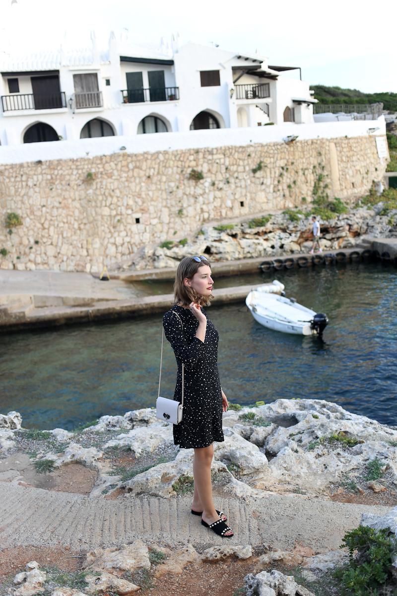 Das letzte Urlausoutfit von Menorca mit einem schwarzen Sternchenkleid. Fotografiert in einem kleinen Fischerdorf an der Südküste der Insel.