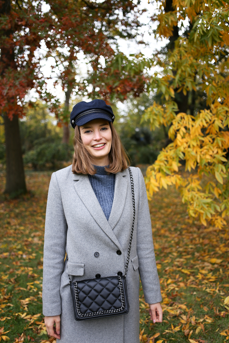 Ein richtiger Novembertag erfordert das passende Outfit. Bloggerin Katharina wählt dafür eine Lederhose, einen Pulli mit Stehkragen sowie Mantel und Baker Boy Mütze.