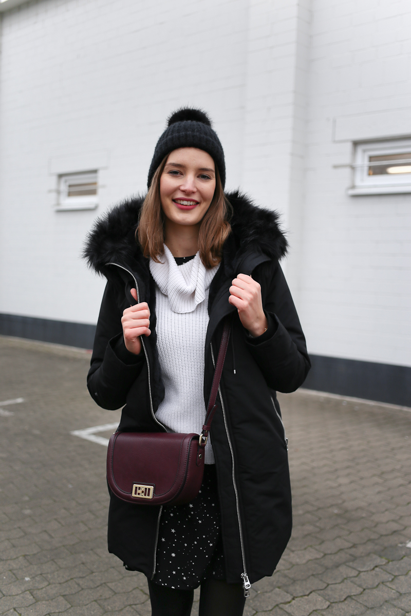 Bloggerin Katharina zeigt ein Winteroutfit mit Sternenkleid, Rollkragenpulli drüber und schwarzen Parka, mit dem sie den frostigen Temperaturen trotzt.